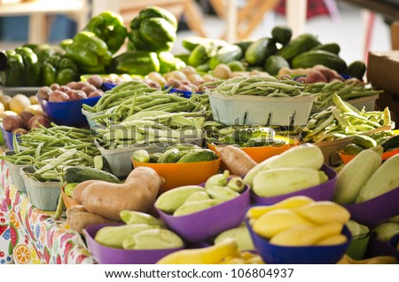 Various healthy vegetables at an open air farmers market featuring beans, potatoes, squash, cucumbers, peppers, and more - stock photo