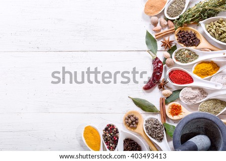 various herbs and spices for cooking on wooden table, top view - stock photo