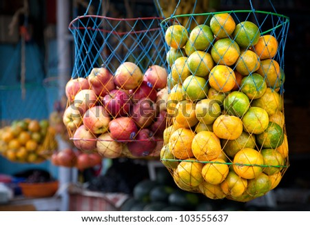 Various Indian oranges and apples in bags at the market, Kumly, Kerala, India - stock photo