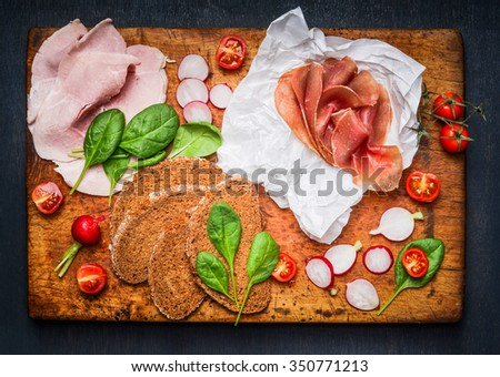 Various ingredients for tasty sandwich with ham and smoked meat on rustic cutting board, top view - stock photo