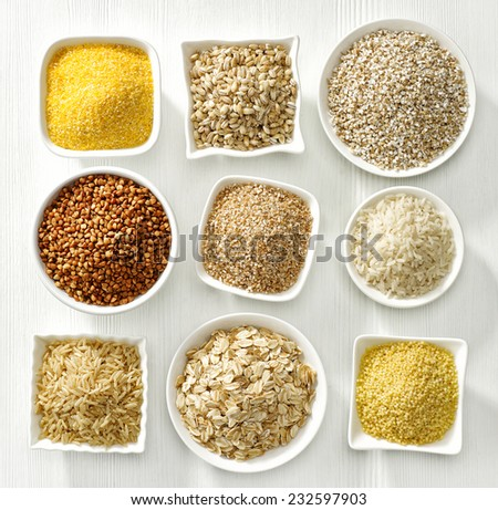 various kinds of cereal grains on white wooden table - stock photo