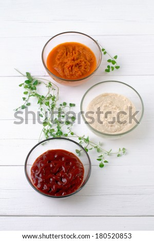 Various kinds of sauces on white wooden background vertical format. - stock photo