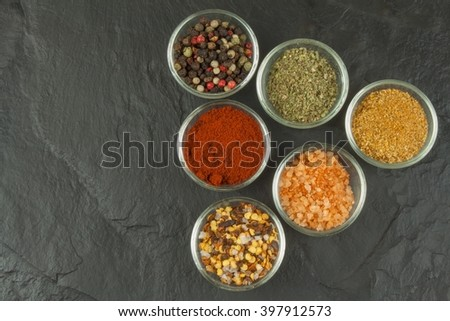 Various kinds of spices in glass bowls on a slate background. Preparation for cooking spicy food. Spices for master cook. The spice trade. Sale of spices in the kitchen. - stock photo