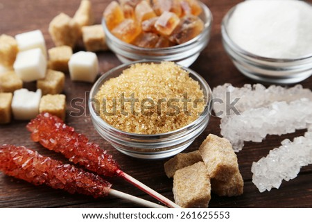 Various kinds of sugar on brown wooden background - stock photo