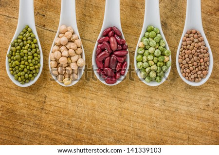 Various legumes on porcelain spoons - stock photo