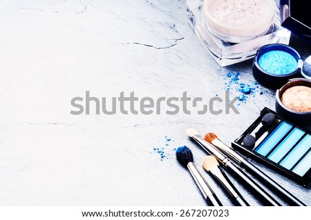 Various makeup products in blue tone with copyspace - stock photo