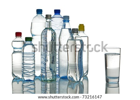 various mineral water bottles and full glass isolated - stock photo
