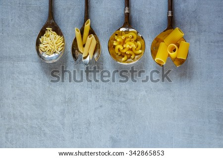Various mix of pasta in old metal spoons over vintage background with space for text. Healthy eating, diet and cooking concept. Top view. Rustic style. - stock photo