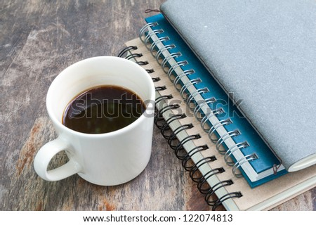 various note book with coffee cup on grunge wood - stock photo