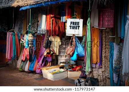 Various of different colorful clothes on Tibetan market and free Tibet banner in India - stock photo