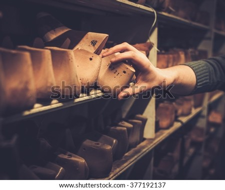 Various of vintage wooden shoe lasts in a row on the old shelves. - stock photo