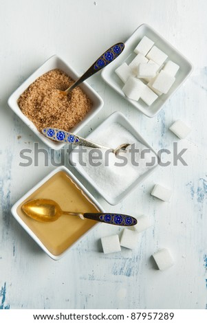 Various of white and brown sugar with honey in white plates on white wooden table - stock photo