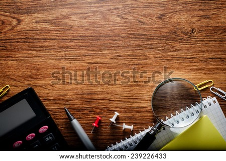 Various Office Supplies with Calculator and Magnifying Glass, Captured at the Bottom Edge of the Frame, with Text Area on Top. Styled with Textured Wooden Background. - stock photo