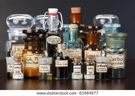Various pharmacy bottles of homeopathic medicine on dark background - stock photo