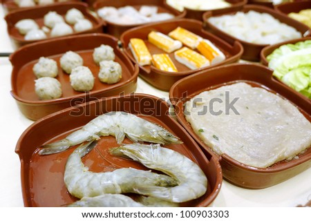 Various plate of Chinese fondue or steamboat set in shallow depth of field. - stock photo
