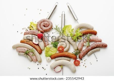 Various raw roast sausages on skewer - stock photo