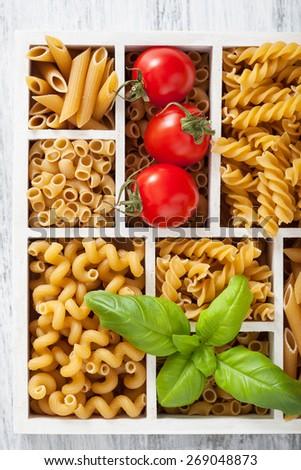 various raw wholegrain pasta in white wooden box - stock photo