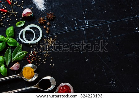 Various sauces in old metal spoons, fresh herbs and spices on dark vintage background with space for text. Vegetarian food, health or cooking concept. - stock photo