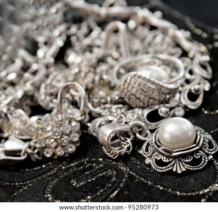 Various silver shining jewellery and closeup pearl on black - stock photo