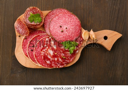 Various sliced salami with garlic, dill and spices on cutting board and wooden table background - stock photo