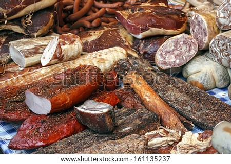 Various smoked meat specialties, placed on a table and exposed on sale. - stock photo