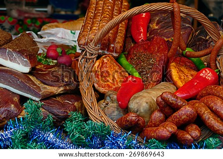 Various smoked sausages specialties, placed on a table and in one wicker basket. Exposed on sale. Specific for December. - stock photo
