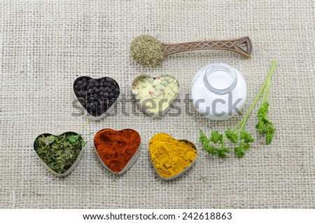 Various spices in heart shaped containers with salt and spoon of oregano - stock photo