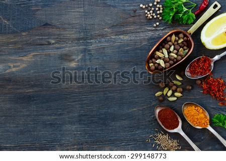 Various spices in old metal scoop and spoons, herbs and spices over dark wooden background with space for text. Cooking ingredients. - stock photo