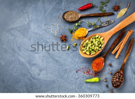 Various Spices powder turmeric, cardamom, chili, paprika, ginger, star anise and clove at blue stone grunge background. Free space for your text  - stock photo