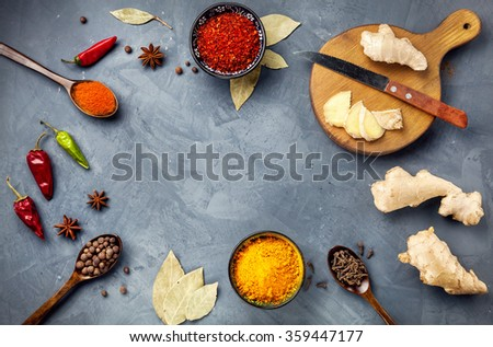 Various Spices powder turmeric, chili, bayberry, bay leaf, ginger on cutting board, cinnamon, cumin, star anise on grey stone background with space for your text, shot from aerial view close-up - stock photo