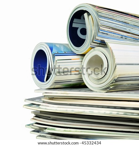 Various stacked and rolled magazines over white - stock photo