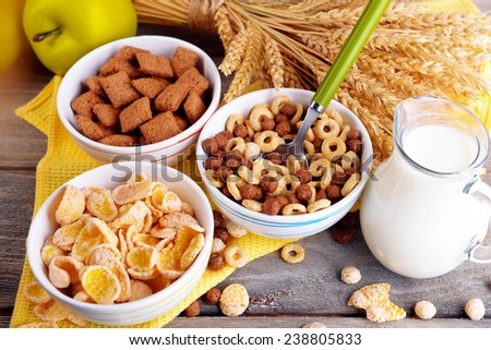 Various sweet cereals in ceramic bowl, fruits and jug with milk on napkin, on color wooden background - stock photo
