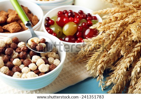 Various sweet cereals in ceramic bowls, fruits and jug with milk on napkin, on color wooden background - stock photo