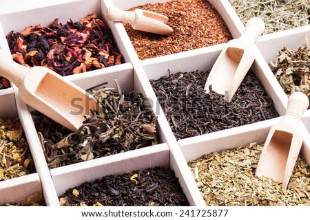 Various tea in a wooden box and scoops - stock photo