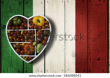 Various tomatoes in heart shaped box on wooden background painted in colors of italian flag. Fresh homegrown organic food. Love for mediterranean, Italian food. Some negative space - stock photo