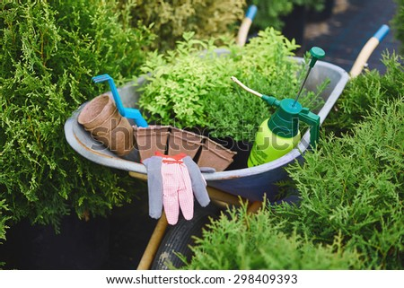 Various tools and objects for gardening in wheelbarrow - stock photo