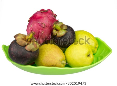 Various tropical fruits in plate isolated on white background - stock photo