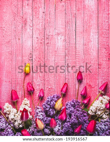 Various tulips and lilac on pink wooden background - stock photo