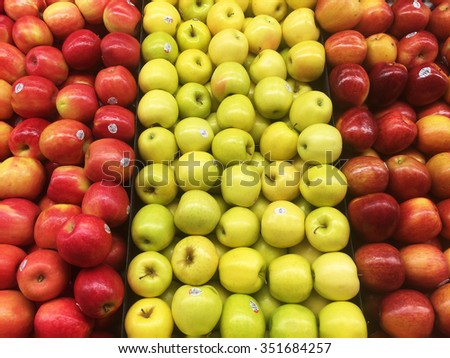 Various types of apples in a grocery store.  The types includes Pink Lady, Golden Delicious and Honey Crisp - stock photo