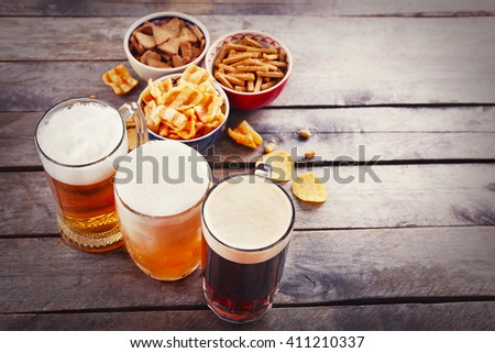 Various types of beer and snacks on wooden table. Retro stylization - stock photo