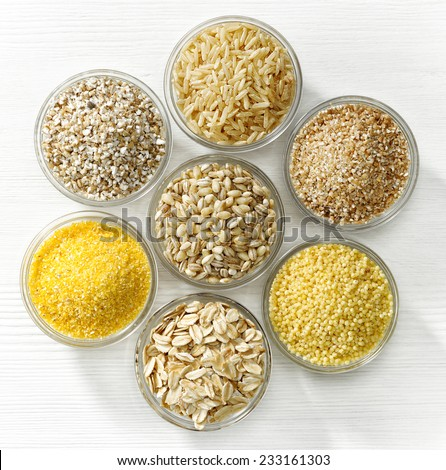 various types of cereal grains on white wooden table - stock photo