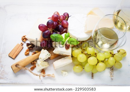 Various types of cheese, cheese board with grapes and wine - stock photo