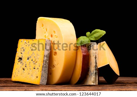 Various types of cheese isolated on black - stock photo