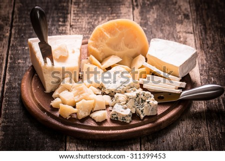 Various types of cheese on wooden table. - stock photo