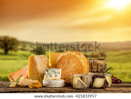 Various types of cheese placed on wooden table, copyspace for text. Beautiful countryside on background - stock photo