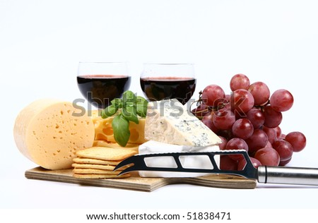 Various types of cheese (swiss, yellow, brie, blue cheese) with red wine, red grapes and crackers and cheese knife on white background - stock photo