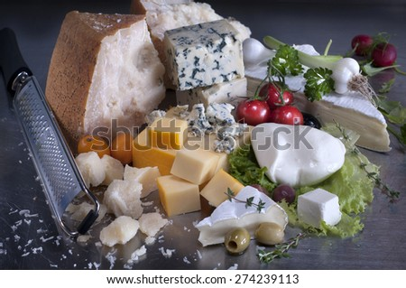Various types of cheese with garlic,cherry tomatoes and olives. - stock photo