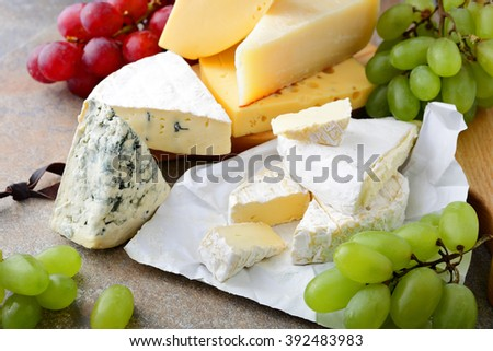 Various types of Cheese with grapes on slate - stock photo