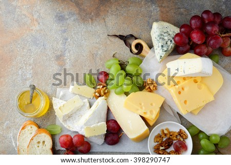 Various types of Cheeses with grapes, honey, bread and walnuts on the slate. Top view - stock photo
