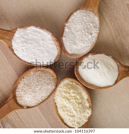 Various types of flour in five wooden spoons - stock photo
